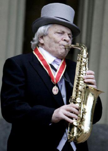 El saxofonista británico, Sir John Dankworth, toca su saxofón en el palacio de Buckinham, Londres