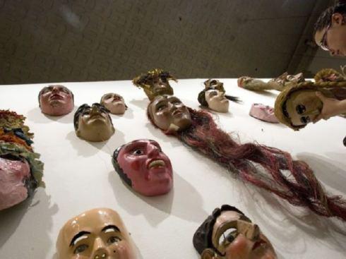"""Una mujer coloca una máscara en la muestra """"Mil y un rostros de México."""