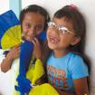 Dos niñas divirtiéndose con unos abanicos de colores